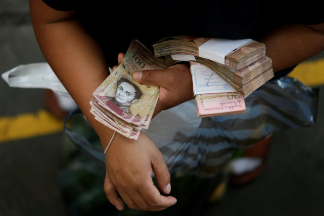 A customer counts Venezuelan bolivar notes at a market in downtown Caracas, Venezuela, December 7, 2016. (Photo by Ueslei Marcelino/Reuters)