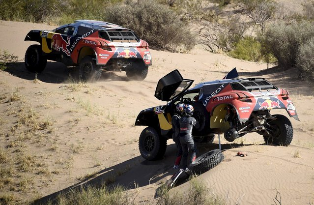 Stephane Peterhansel (L) of France and co-pilot Jean Paul Cottret change a tire of their Peugeot as Carlos Sainz of Spain drives his Peugeot past them during the ninth stage of the Dakar Rally 2016 near Belen, Argentina, January 12, 2016. (Photo by Franck Fife/Reuters)