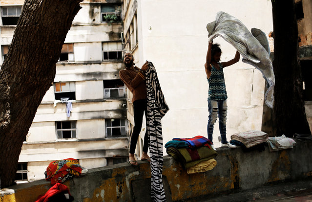 Rodrigo (L), 26, and Wam, 24, who are among members of lesbian, gay, bisexual and transgender (LGBT) community, that have been invited to live in a building that the roofless movement has occupied, shake blankets, in downtown Sao Paulo, Brazil, November 8, 2016. (Photo by Nacho Doce/Reuters)