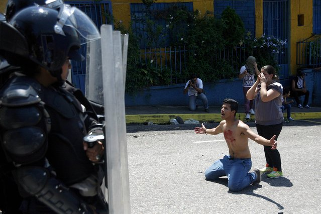 A boy with blood on his chest kneels in front of police after 14-year-old student Kluiver Roa died during a protest in San Cristobal February 24, 2015. Roa was killed during a protest in the western city of San Cristobal on Tuesday, a state official said, as tensions rise in Venezuela amid an economic crisis and a government crackdown on the political opposition. The circumstances surrounding his death remained unclear, Colonel Ramon Cabezas, head of citizen security for the state of Tachira, told reporters. Roa died amid violent clashes between protesters and police near the home of Tachira's ruling party governor after a police officer shot at the ground, Cabezas added, though it was unclear whether he had died from a bullet wound. (Photo by Carlos Eduardo Ramirez/Reuters)