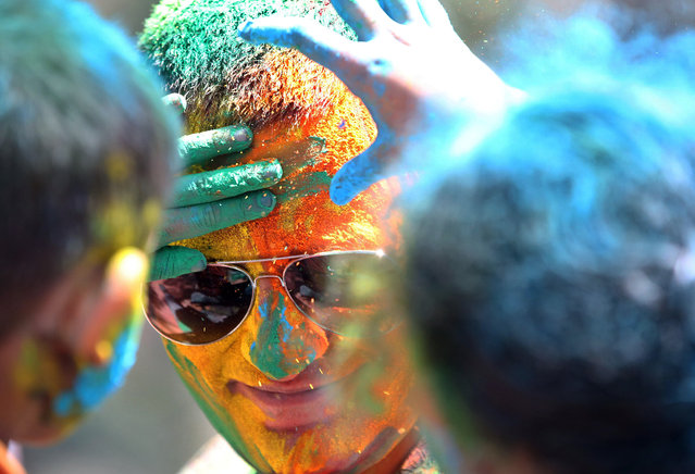 Children smear the face of a man with coloured powder during celebrations marking Holi, the Hindu festival of colors, in Mumbai, India, Friday, March 6, 2015. Holi, India's joyful and colorful celebration of the arrival of spring along with several religious myths and legends, has long ago ceased to be only a Hindu festival. The streets and lanes across most of India turn into a large playground where people off all faiths throw colored powder and water at each other. (AP Photo/Rajanish Kakade)