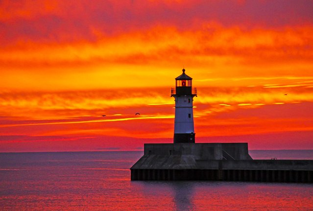 The sky above Lake Superior is filled with color at dawn as seen from Canal Park in Duluth, Minn, on Oktober 17, 2013. (Photo by Andrew Krueger/The Duluth News-Tribune)