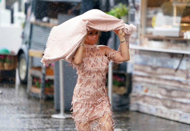 Racegoers try to shelter from the rain during day one of the Cazoo Derby Festival at Epsom Racecourse on Friday, June 4, 2021. (Photo by John Walton/PA Images via Getty Images)
