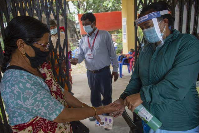 A Nepalese health worker sanitizes the hands of a woman as she arrives gets inoculated against the coronavirus in Kathmandu, Nepal, Tuesday, June 8, 2021. Nepal resumed its stalled coronavirus vaccination campaign on Tuesday with 1 million doses given by China after the Himalayan nation made international pleas for help with a shortage of doses. (Photo by Bikram Rai/AP Photo)