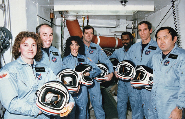 """Crew members of mission STS-51L stand in the White Room at Pad 39B following the end of the Terminal Countdown Demonstration Test (TCDT). From left to right they are: Teacher in Space Participant, Sharon """"Christa"""" McAuliffe, Payload Specialist, Gregory Jarvis, Mission Specialist, Judy Resnik, Commander Dick Scobee Mission Specialist, Ronald McNair, Pilot, Michael Smith and Mission Specialist, Ellison Onizuka. (Photo by NASA)"""