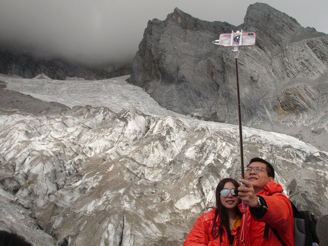 This September 22, 2018 photo shows tourists posing for a selfie before the Baishui Glacier No.1 atop of the Jade Dragon Snow Mountain in the southern province of Yunnan in China. Scientists say the glacier is one of the fastest melting glaciers in the world due to climate change and its relative proximity to the Equator. It has lost 60 percent of its mass and shrunk 250 meters since 1982. (Photo by Sam McNeil/AP Photo)