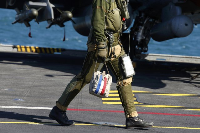 A pilot walks past a Rafale fighter jet prior to a mission aboard France's Charles de Gaulle aircraft carrier sailing in the Gulf, January 28, 2016. (Photo by Philippe Wojazer/Reuters)