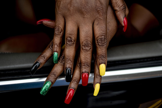 Flint resident Tracy Palmer shows off her Juneteenth-inspired nails during one of two parades celebrating the holiday on Saturday, June 19, 2021 along Saginaw Street in downtown Flint, Michigan. (Photo by Jake May/MLive.com via AP Photo)
