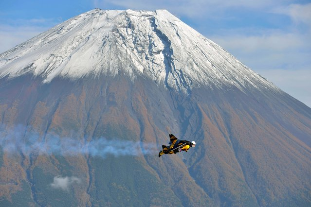 In this photo taken Wednesday, Oct. 30, 2013 and provided by Breitling, Yves Rossy, known as the Jetman, flies by Mount Fuji in Japan. The Swiss aviator jumped from a helicopter at an altitude of 3,600 meters (11,811 feet) and successfully flew the jet-powered carbon-Kevlar Jetwing around the 3,776-meter (12,388-foot)-tall mountain, Japan's highest peak, which was recognized as a UNESCO World Heritage site in June. (Photo by Katsuhiko Tokunaga/AP Photo/Breitling)