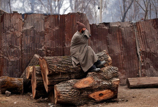A man sits on a log on a cold winter morning in Srinagar, December 15, 2016. (Photo by Danish Ismail/Reuters)