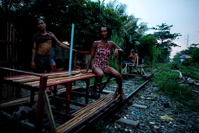 """This picture taken on October 19, 2018 shows """"trolley boy"""" couple Tyson Aguha (L) and Joan Acebo waiting for passengers along a train track in Manila, Philippines. (Photo by Noel Celis/AFP Photo)"""
