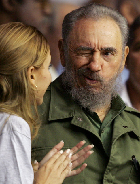 Cuban President Fidel Castro (R) winks at a woman at the graduation of hundreds of Cuban art students at Havana's Sports City in this October 28, 2005 file photo. (Photo by Claudia Daut/Reuters)
