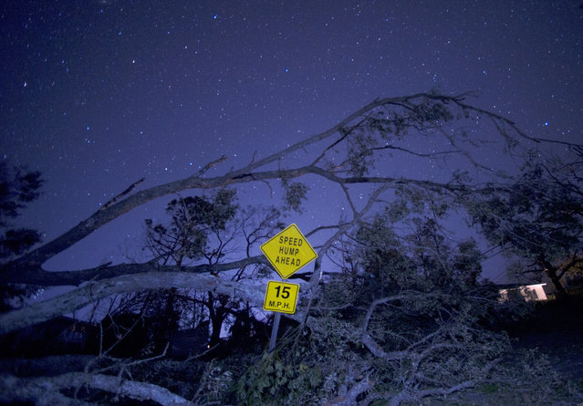The night sky shines over a downed tree and road sign on Thursday, October 11, 2018, in Panama City, Fla. Hurricane Michael, moving through the Florida panhandle community the previous day, knocked down power lines in most of the city. (Photo by Patti Blake/Northwest Florida Daily News via AP Photo)