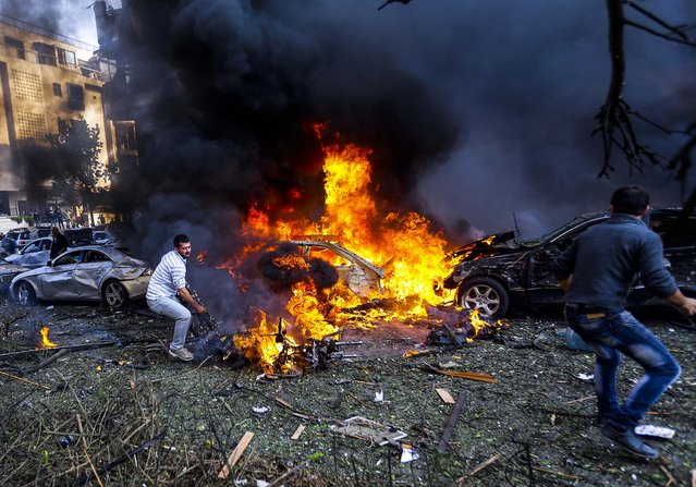 Men run to remove dead bodies from burned cars, at the scene of two explosions near the Iranian Embassy killing at least 23 people and injuring146 people, on November 19, 2013. On Twitter, a radical Sunni group claimed responsibility for the attacks, saying similar assaults would continue until the Iran-supported Shiite group Hezbollah stops sending fighters to help Syrian government forces. (Photo by Hussein Malla/Associated Press)