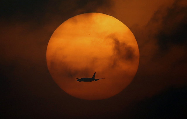 An airplane flies while is seening from the track of Meydan racecourse during preparations for the Dubai World Cup 2015 in Dubai, United Arab Emirates, March 24, 2015. (Photo by Ali Haider/EPA)