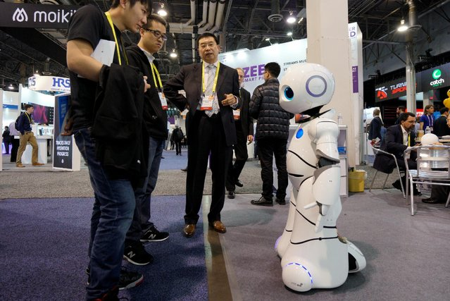 Shengguang Zhang (C) talks about the Baymax Intelligent Service Robot with showgoers at the Robotics Marketplace at CES in Las Vegas, U.S., January 5, 2017. (Photo by Rick Wilking/Reuters)