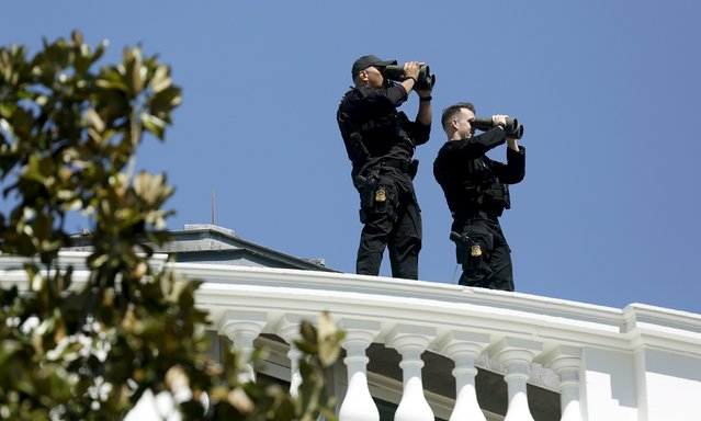 Members of the White House Counter Assault Team (CAT) watch the area around the White House from the roof of the building during the annual Easter Egg Roll in Washington April 6, 2015. (Photo by Gary Cameron/Reuters)