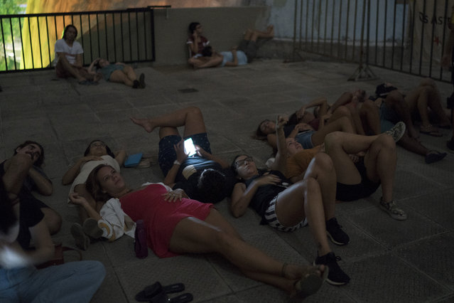 People watch a blood moon from a rooftop of a planetarium during a lunar eclipse in Rio de Janeiro, Brazil, Monday, January 21, 2019. It's also the year's first supermoon, when a full moon appears a little bigger and brighter thanks to its slightly closer position to Earth. (Photo by Leo Correa/AP Photo)