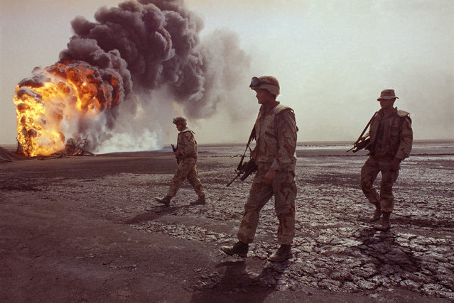 In this March 7, 1991 file photo, a U.S. Marine patrol walks across the charred oil landscape near a burning well during perimeter security patrol near Kuwait City. Twenty five years after the first U.S. Marines swept across the border into Kuwait in the 1991 Gulf War, American forces find themselves battling the extremist Islamic State group, born out of al-Qaida, in the splintered territories of Iraq and Syria. The Arab allies that joined the 1991 coalition are fighting their own conflicts both at home and abroad, as Iran vies for greater regional power following a nuclear deal with world powers. (Photo by John Gaps III/AP Photo)