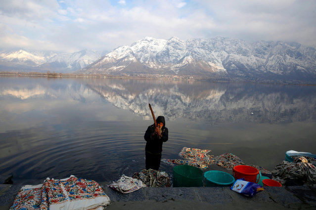 A Kashmiri laundry man washes clothes with the snow-covered mountains in the backdrop at Nageen Lake on a sunny day on the outskirts of Srinagar, the summer capital of Indian Kashmir, 27 January 2019. Srinagar-Jammu highway which connects Indian Kashmir with the rest of the world was reopened partially for traffic after six days of closure. (Photo by Farooq Khan/EPA/EFE)