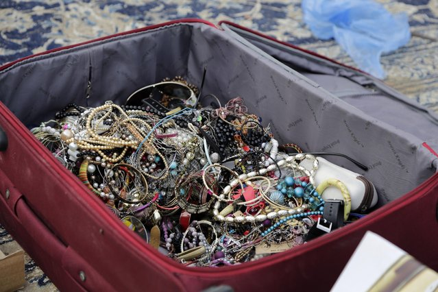In this April 16, 2015 photo, costume  jewelry is on display for sale at al-Aqeeliya open-air auction market in Riyadh, Saudi Arabia. A man came with the suitcase full of beaded jewelry and sold the whole bag to the auction winner, who had just a few moments to inspect its contents before buying. (Photo by Hasan Jamali/AP Photo)