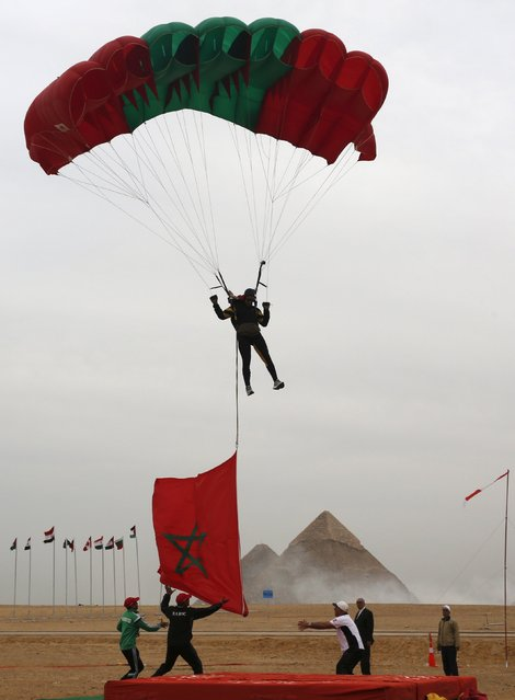 A paratrooper from Morocco with a parachute in the colours of the Moroccan flag, takes part in the opening of the Egyptian International Parachuting Championship, which is organized by Egyptian Parachuting and Air Sports Federation (EPAF), in front of the Great Pyramids of Giza, Egypt March 2, 2016. (Photo by Amr Abdallah Dalsh/Reuters)