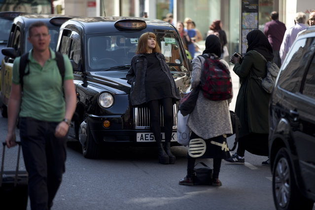 A woman leans back on a cab to pose for  pictures for her friends as London taxi drivers block the traffic during their two-hour protest on Oxford Street in London, Tuesday, April 21, 2015. The protest Tuesday was organized by the United Cabbies Group over issues including illegal minicab touting and threats to regulations. (Photo by Matt Dunham/AP Photo)