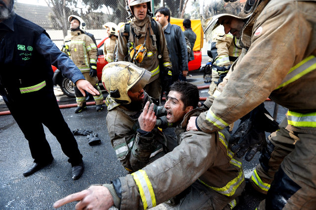 Iranian fire fighters condole one of their colleagues in Tehran, Iran, 19 January 2017. Media reported that major commercial building in Tehran has collapsed after hours of a severe fire, according to Iranian state media. At least 30 deaths, all firefighters were trapped on upper floors of buildings that have collapsed. (Photo by Abedin Taherkenareh/EPA)