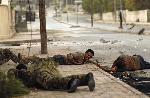 Members of the Al-Baraa bin Malek batallion, part of the Free Syria Army's Al-Fatah brigade, duck to the ground as they pull a man (R) who was shot by a sniper twice in the Bustan al-Basha district of the northern city of Aleppo on October 20, 2012. (Photo by Javier Manzano/AFP Photo)