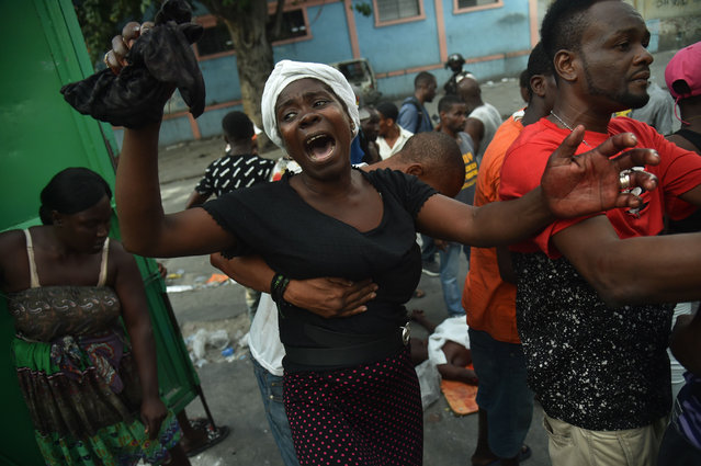 A mother cries beside the body of her dead son who was shot during clashes between Haitian police and demonstrators near to the National Palace in Port-au-Prince, on February 9, 2019. Demonstrators are demanding the resignation of Haitian President Jovenel Moise and protesting the Petrocaribe fund which for years Venezuela supplied Haiti and other Caribbean and Central American countries with oil at cut-rate prices and on easy credit terms. But investigations by the Haitian Senate in 2016 and 2017 concluded that nearly $2 billion from the program was misused. (Photo by Héctor Retamal/AFP Photo)