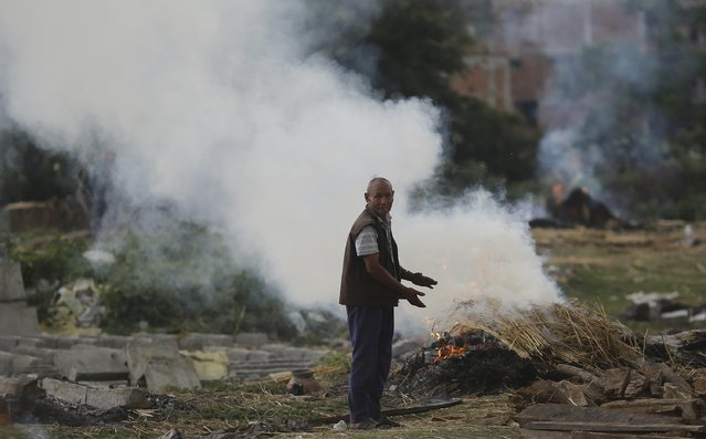 A man stands next to the burning pyre of a family member at a cremation ground in the aftermath of Saturday's earthquake in Bhaktapur, Nepal April 27, 2015. (Photo by Adnan Abidi/Reuters)