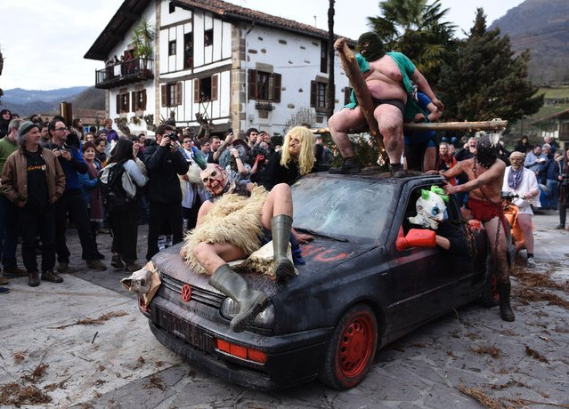 Disguised participants strike poses on a car during the ancient carnival of Ituren, in the northern Spanish Navarra province on January 30, 2017. The yearly three day festivities, revolving mainly around agriculture and principally sheep hearding, run on the last Sunday, Monday and Tuesday of January where Navarra Valley locals from two villages dress up and participate in a variety of activites as they perform a pilgrimage through each village. (Photo by Ander Gillenea/AFP Photo)