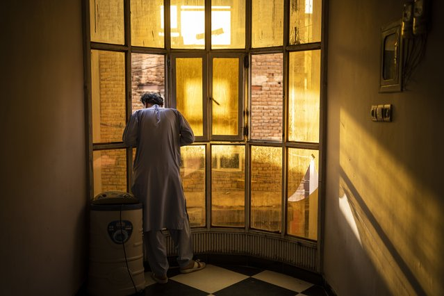 An Afghan singer looks out a window in Kabul, Afghanistan, Tuesday, September 14, 2021. About a month after the Taliban seized power in Afghanistan, the music is starting to go quiet. The last time that the militant group ruled the country, in the late 1990s, it outright banned music. (Photo by Bernat Armangue/AP Photo)