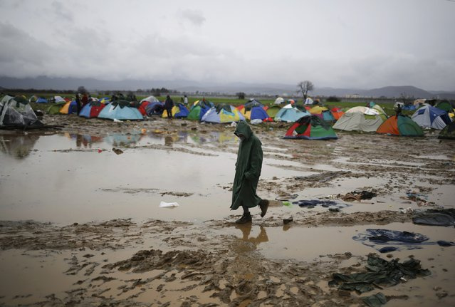 A migrant walks in a mud at a makeshift camp on the Greek-Macedonian border, near the village of Idomeni, Greece March 10, 2016. (Photo by Stoyan Nenov/Reuters)