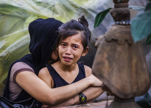 A mother and her daughter cry as a demolition crew demolishs their shanty at the sprawling community of informal settlers in Quezon city northeast of Manila, Philippines, on January 28, 2014. Tuesday's demolition was without any resistance compared to yesterday when residents pelt riot police with rocks, empty bottles and home made explosives and injured about a dozen people and police arresting nine residents. (Photo by Bullit Marquez/Associated Press)