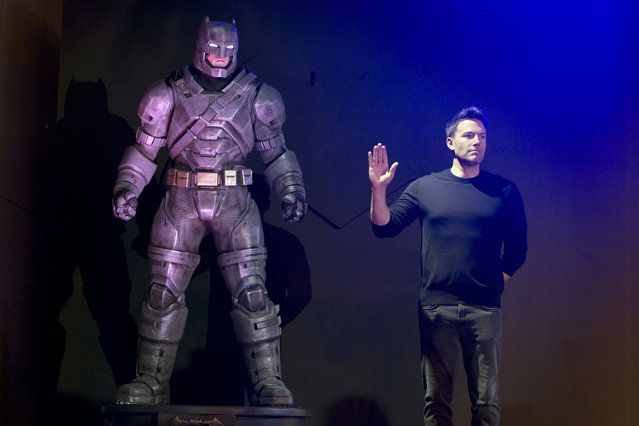 """Actor Ben Affleck poses with a statue of Batman during a press conference for the movie """"Batman v Superman: Dawn of Justice"""" in Beijing, China, Friday, March 11, 2016. (Photo by Ng Han Guan/AP Photo)"""