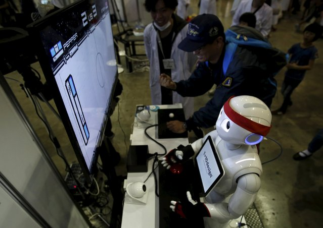 "SoftBank Corp's humanoid robot named ""Pepper"" plays a video game against a visitor at a booth during Niconico Chokaigi 2015 in Makuhari, east of Tokyo, Japan April 26, 2015. (Photo by Yuya Shino/Reuters)"