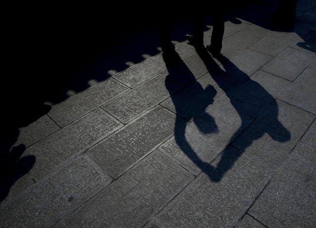 A man and a woman cast their silhouettes as they perform square dancing at a park square in Beijing, China, April 13, 2015. (Photo by Kim Kyung-Hoon/Reuters)