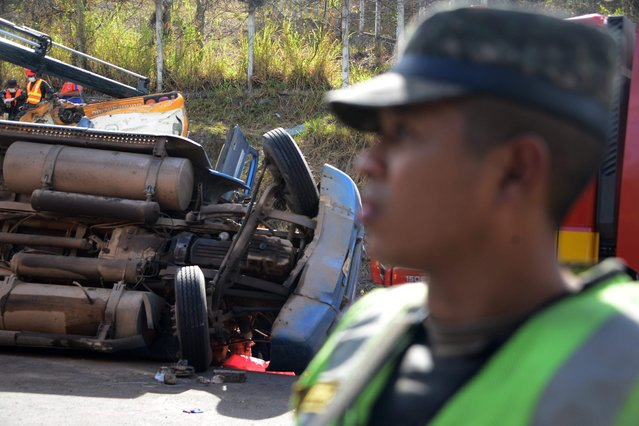 A military policeman stands next to a truck after a crash with a bus on the road that links the Honduran capital with the south of the country, near Germania, 11 km south of Tegucigalpa on February 5, 2017. (Photo by Orlando Sierra/AFP Photo)
