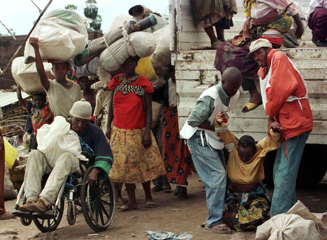 Rwandan Red Cross workers help refugees as they crossed from the border into Gisenyi, Rwanda from the former Zaire, now the Democratic Republic of the Congo, November 17, 1996. (Photo by Reuters/Stringer)