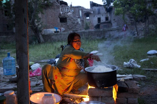 A woman who lost her house in the April 25 earthquake cooks rice in Sakhu, Nepal, Wednesday, May 6, 2015. The  earthquake killed thousands and injured many more as it flattened mountain villages and destroyed buildings and archaeological sites in Kathmandu. (Photo by Bernat Amangue/AP Photo)