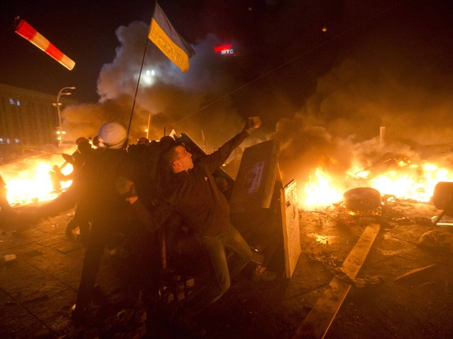 Anti-government protesters clash with riot police in Kiev's Independence Square. (Photo by Efrem Lukatsky/AP Photo)
