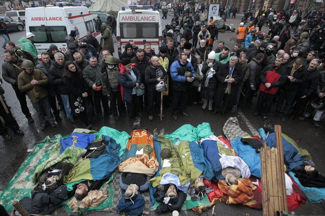 Activists pay respects to protesters killed in clashes with police, in Kiev's Independence Square, the epicenter of the country's current unrest, Thursday, February 20, 2014. Fierce clashes between police and protesters, some including gunfire, shattered a brief truce in Ukraine's besieged capital Thursday, killing numerous people. (Photo by Sergei Chuzavkov/AP Photo)