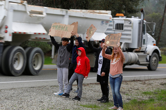 Children hold signs thanking truck drivers hauling rocks to the Lake Oroville Dam after an evacuation was ordered for communities downstream from the dam in Oroville, California, U.S. February 13, 2017. (Photo by Jim Urquhart/Reuters)
