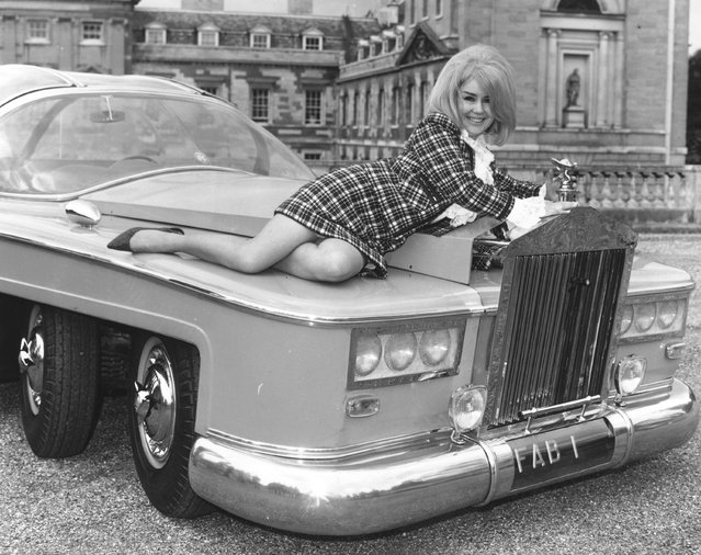 """Actress Penny Snow reclines on the bonnet of a pink, six-wheeled Rolls Royce outside Woburn Abbey. The car is a specially built, full-size replica of the vehicle """"FAB 1"""" owned by the character Lady Penelope in the puppet television series """"Thunderbirds"""". 1968. (Photo by Joe Bangay/Express/Getty Images)"""