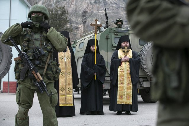 Orthodox monks pray next to armed servicemen near Russian army vehicles outside a Ukrainian border guard post in the Crimean town of Balaclava March 1, 2014. (Photo by Baz Ratner/Reuters)