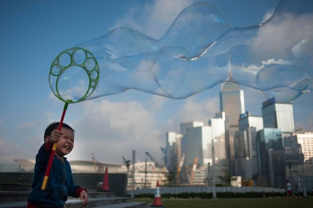A boy waves a wand of bubbles up in the air at Tamar Park outside of Central Government Complex at Admiralty district on November 22, 2014 in Hong Kong.   In a random poll of 513 people conducted by the University of Hong Kong, support for the movement had decreased with 83% of those surveyed saying the eight week occupation should end. (Photo by Anthony Kwan/Getty Images)