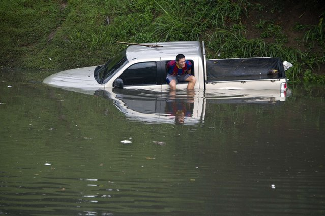 A man sits on the window of his flooded truck in Cali, Colombia on March 12, 2014, during heavy rains. The IDEAM (Institute of Hydrology, Meteorology and Environmental Studies of Colombia) announces a strong rainy season for the next three months in the country. (Photo by Luis Robayo/AFP Photo)