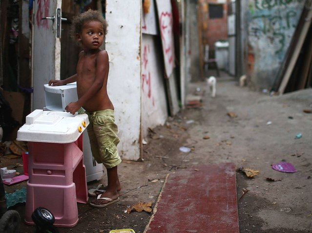 A young resident stands next to a children's kitchen playset in an impoverished area in the unpacified Complexo da Mare slum complex. (Photo by Mario Tama/Getty Images)