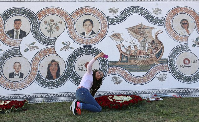 A girl takes a selfie in front of the mosaic portraits of the victims of a militant attack on the Bardo national museum in March 2015 that killed 21 people, at the museum in Tunis, Tunisia March 19, 2016. (Photo by Zoubeir Souissi/Reuters)